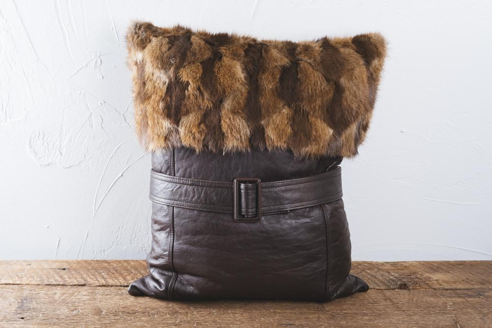 Quite original, this rectangular cushion is composed of shaved beaver fur and leather and decorated with a belt. Dimensions 55x25.